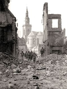 British soldiers pick their way through the ruins at Cambrai, 1918.