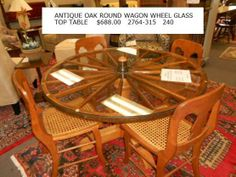 Antique wagon wheel glass table. W/ Chairs www.eliterepeatfurniture.com
