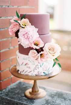A three-tiered floral wedding cake, with two marsala-hued top tiers and decorated with fresh flowers by @jarcakery | Brides.com