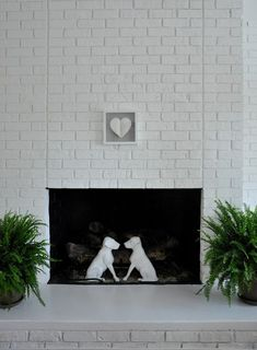 [image above: I fell in love with these andirons after seeing them in House Beautiful. They are completely apropos for our house, given that we have two labs. I painted them white to be more in keeping with the house vibe.]