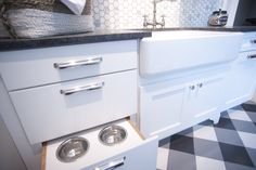 Laundry Room: Dog Bowl Drawer / Design by Dalton Carpet One  Wellborn Cabinets- Finish: Glacier MDF Door Style: Bishop Countertops: Granite, Brushed Steel Gray Floor Tile: Retro Black, White, Dark Gray Grout: Pearl Gray Backsplash: Calcutta Gold, 2x2 hexagon Grout: Mapei Pewter Photo by: Dennis McDaniel