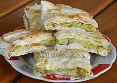 Пирог из лаваша с курицей, рисом, овощами и зеленью, испеченный в духовке.