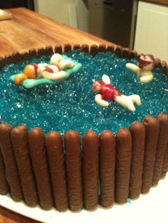 Swimming pool cake, cake base, blue jelly pool and chocolate finger pool walls and marzipan family.