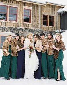 These bridesmaids wore jewel-toned Dessy dresses with feather hairpieces and jewelry designed and created by the bride herself. The matrons of honor -- her sisters -- wore sapphire, while the other attendants wore emerald. All kept warm against Colorado's February chill with vintage fur stoles.