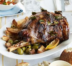 Slow-cooked Greek Easter lamb with lemons, olives & bay. This authentic dish of meltingly tender leg of lamb is roasted with garlic, lemon and potatoes for an irresistible Sunday lunch centrepiece