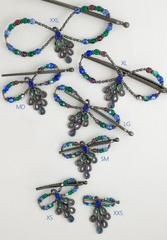 Lilla Rose Inc - Colors on Parade Peacock is magnificent with shades of emerald, sapphire, and purple. Its tail comes alive with dangling feathers to compliment each bead that is highlighted with a touch of aurora borealis for a brilliant affect. The black nickel plating adds a richness to complete this radiant design. Look for the matching Hair Band for a fun updo!