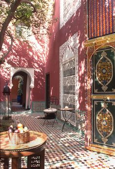 The Moroccan sun bathing a beautiful courtyard in a traditional Moroccan home (Riad). These large hand painted doors are magnificent! #Moroccan #Doors #Handmade.