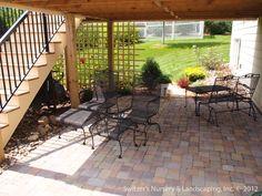 Mosaic cobblestone patio set just adjacent to deck.