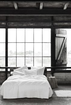 What delight in the rustic simplicity of this bedroom with the big barn door inviting one to awake and begin to explore the day ahead.  I've always wanted a bedroom that leads you to the outside world upon waking and this one does the job perfectly.