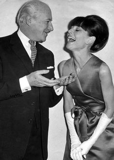 """Cecil Beaton photographed with Audrey Hepburn during a press reception at the Savoy Hotel for some of the stars of """"My Fair Lady"""" in London (England), on January 19, 1965. Audrey was wearing: Cocktail dress: Givenchy (emerald green, of shantung with a satin ribbon at the waist, of his haute couture collection for the Autumn/Winter 1964/65). Earrings: Cartier."""