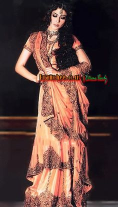 Atomic Tangerine (upper layer crinkle chiffon and under layer silk) flared lehenga having wide cramped embellished hemlines of both the layers. Floral vertical embellishment strips on both layers and small ornamental motifs all over. Upper layer has dipped hem from back. Fully lined. Concealed zip closure on side.