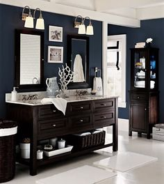 The walls are sea blue - the use of dark furniture, which works as the room seems to be spacious. The light flooring, trim and countertops, as well as the towels and decorative accessories, make for a contrast with the blue.