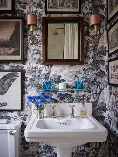 Powder room with botanical wallpaper, artwork and pops of blue.