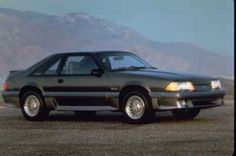 1987 Mustang.There was a significant restyling for 1987. Mustangs received the drooped nose, and thus all radiator breathing was from under the front bumper. Headlights were changed to aero-headlamps with halogen bulbs. Visually, the GT differed from the base LX model with multilouvered taillights, front and rear air dams, and side-aerodynamic valence with scoops to front and rear brakes. The former three door sedans were now called two door hatchbacks.
