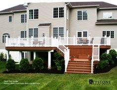 Trex Saddle decking with White Vinyl Posts, Rails and Balusters. Built by Keystone Custom Decks.