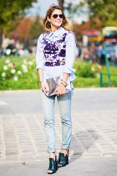 A button-down blouse is layered with a floral shell tank, boyfriend jeans, peep-toe heels, and a metallic clutch