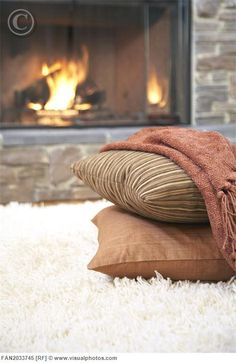 pillows and rug in front of the fire
