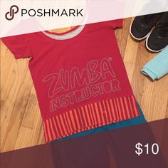 Zumba instructor short-sleeve top Instructor top with banded bottom giving it a relaxed fit at waist/tummy. Low scoop neck can be worn off one shoulder. Only worn a few times - never put in dryer. Large print is on back, front is grey with small logo. Can be worn backwards - I did Zumba wear Tops Tees - Short Sleeve