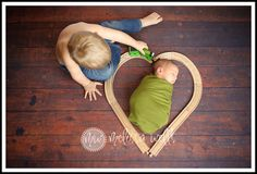 such a cute idea for a picture of big brother and baby using props from the toy room