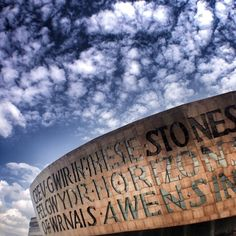 "Wales Millennium Centre, Cardiff Bay, Cardiff, South Wales, UK - Inscribed on the front of the dome, above the main entrance, are two poetic lines, written by Welsh poet Gwyneth Lewis. The Welsh version is 'Creu Gwir fel gwydr o ffwrnais awen', which means ""Creating truth like glass from the furnace of inspiration"". The English is 'In These Stones Horizons Sing'.The lettering is formed by windows in the upstairs bar areas and are internally illuminated at night."