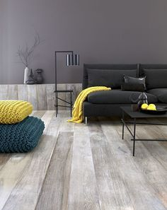 Ash coloured floorboards and partial wall panels. Black couch