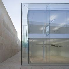 Office in Spain by architect Alberto Campo Baeza, walls made entirely of glass behind a sandstone enclosure