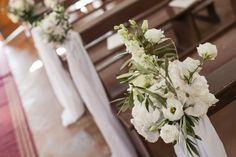 Beautifully simple pew ends lining the aisle, with white fabric draping to the floor