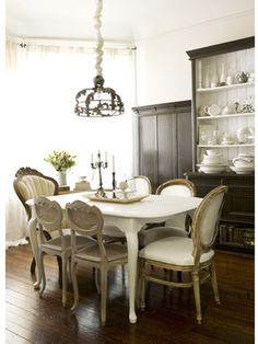 Mix and Match Vintage ... Neutral hues unite the variety of vintage chairs surrounding the dining table. The pendant lamp is from a Paris street market, and the china cabinet at a California antiques store.