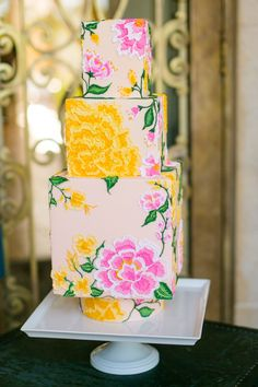 Square-tiered cake covered in embroidered-looking flowers