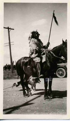 """Black and white photograph captioned """"Blackfoot Brave with scalps"""" featuring a Blackfoot man on horseback in traditional costume, holding a stick decorated with a scalp. Dog with travois in background. Fort Macleod, Alberta, Canada. Date of creation 1925. University of Saskatchewan Libraries Special Collections."""