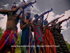 Mursi warriors in bright cloth pose AK-47 guns omo-valley tribes ethiopia