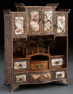 A VERY FINE JAPANESE SILVER AND SHIBAYAMA CABINET, MEIJI PERIOD. The silver case with floral repoussé panels containing 4 hinged doors above 5 drawers each inset with ivory panels decorated in the Shibayama style with birds and floral blossoms in carved coral and mother of pearl. The interiors decorated in Nasiji and gold hirdmaki-e, inlaid silver chop on base. Height 10 inches (25 cm).