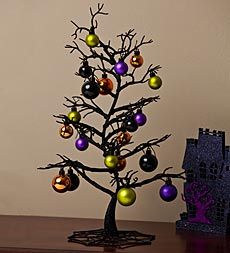It's a Christmas tree worthy of Tim Burton! Used as a centerpiece or on an end table or coffee table, our decorative black Halloween Tabletop Tree becomes a spooky focal point in any room. Comes with 20 ornaments in Halloween orange, black, purple and gold.
