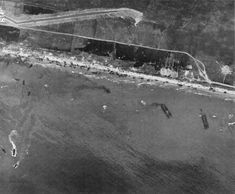 Aerial view of Omaha Beach, Normandy, France, taken 6 June 1944, showing landing of two infantry regiments 18th and 115th, vehicles, and landing craft.