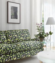 """Gray-on-gray striped """"Magnus"""" wallpaper by Sandberg is the canvas for a brightly patterned sofa."""
