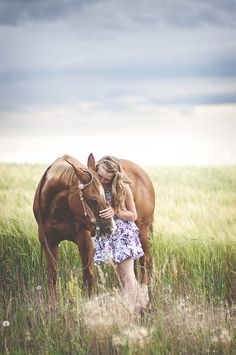 Lovely portrait. Girl with her horse in the tall grass.