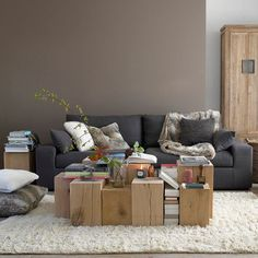 modern gray sofa, set of square wood tree trunks as coffee table: