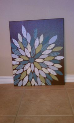 "Flower Wall Art - REMAKE  Canvas painted a solid color, 6 sheets of scrapbook paper cut into 2 in squares and then into ""petals"". Super easy, cheap and looks like professional artwork :)"