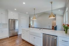 Modern gourmet kitchen with marble countertops, brass pendant lights, & stainless steel appliances!