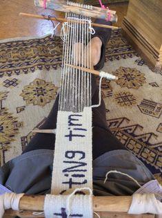 Sarah Swett weaving tapestry on a backstrap loom