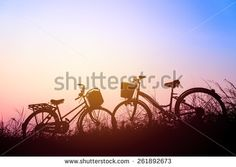 beautiful landscape image with Silhouette Bicycle at sunset - stock photo