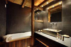 plafond poutre apparente dans la salle de bain, carrelage mural gris anthracite et vasque en acier inox