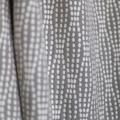 A pretty, woven, warm medium grey fabric with creamy white dots in a soft, organic striped pattern.Perfect for upholstery, throw pillows, cushions, roman blinds