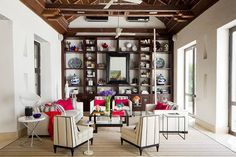 """When designer Richard Mishaan outfitted the living room of his Cartagena vacation home, he imagined that the shelves were filled with the personal effects of """"a historic king's most trusted sea captain."""" Mishaan created this highly curated assemblage using Pre-Colombian artifacts, antique rosaries, Fornasetti plates and gilded jewelry."""