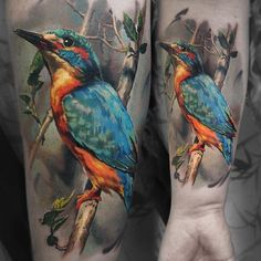Realism piece with a Kingfisher perched on a branch with a desaturated background, done on girls forearm by Valentina Ryabova , an artis...