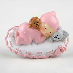 Tierno imán con un bebé dormido sobre un almohadón con dos peluches a los lados