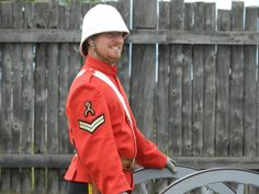 A North-West Mounted Police corporal with the Rough Rider insignia waits by the cannon for his orders at Fort Battleford National Historic Site.