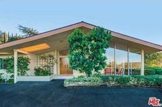 This midcentury modern home in Sherman Oaks has a gable roof, exposed structure, walls of glass, skylights, double doors and simple furniture.