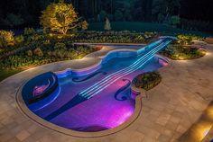 Pool Design in Geigenform-Terrassenboden mit steinen-Begrünung-blumenbeete