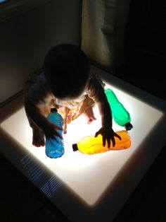 Light table play with babies. Water bottles filled with half colored water and half vegetable oil. - via Reggio Children Inspired ≈≈